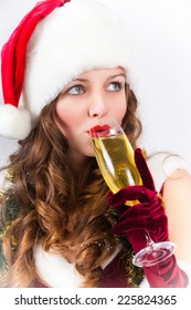 Beautiful girl in Santa Claus hat with champagne glass