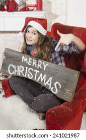 Beautiful girl in Santa Claus hat showing wooden signboard with Merry Christmas