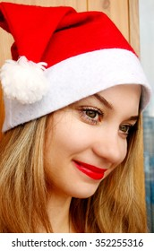 Beautiful girl Santa Claus, make a wish before Christmas and New Year night. Red white hat cap with bubo and fur. Red lips