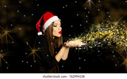 Beautiful girl with Santa hat blowing golden dust and stars happy holiday make wishes concept