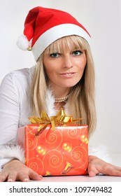 beautiful girl in santa hat with present