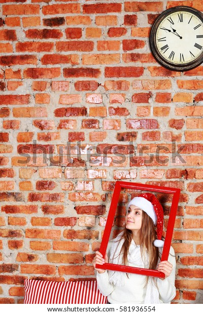 Beautiful girl in santa hat sitting on the floor, looking away. Holding frame in hands