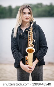 Beautiful girl with a saxophone on the beach