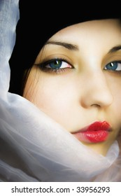 The beautiful girl in a scarf with blue eyes