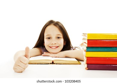 Beautiful girl with school books on the table, showing OK sign. Isolated on white background