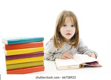Beautiful girl with school books on the table, reading.