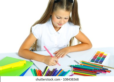 A beautiful girl in a school form drawing a marker, isolated on a white background