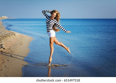Beautiful Girl in sea style having fun on a beach. Travel and Vacation. Freedom Concept. Sensual blonde beautiful woman, Girl with perfect body and long healthy hair,Marine style