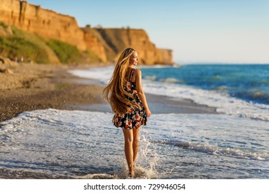 Beautiful Girl in sea style having fun on a beach. Travel and Vacation. Freedom Concept. Sensual blonde beautiful woman, Girl with perfect body and long healthy hair,