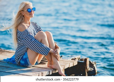Beautiful Girl in sea style sitting on wooden bridge. Travel and Vacation. Freedom Concept. Sensual blonde beautiful woman, Girl with perfect body and long healthy hair,Marine style