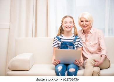 Beautiful girl and senior woman sitting together with laptop and smiling at camera