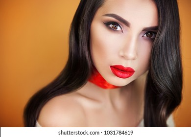 a beautiful girl with sensual bright red lips on an orange background, a red ribbon on her throat does not leave anyone indifferent, everyone looking into her brown eyes.