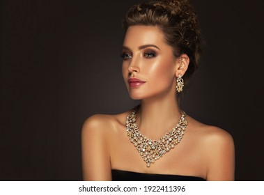 Beautiful girl with set jewelry .   Elegant woman with cute hairstyle in a necklace with  earrings . Beauty and accessories.