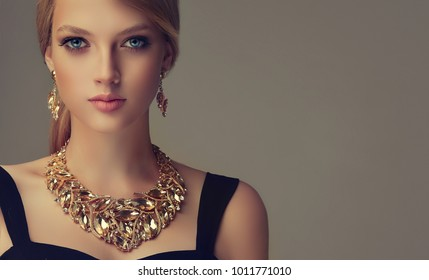 Beautiful girl with set jewelry .   Woman in a necklace with earrings . Beauty and accessories.