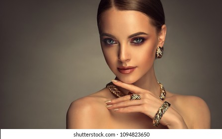 Beautiful girl with set jewelry .   Woman in a necklace with a ring, earrings and a bracelet. Beauty and accessories.