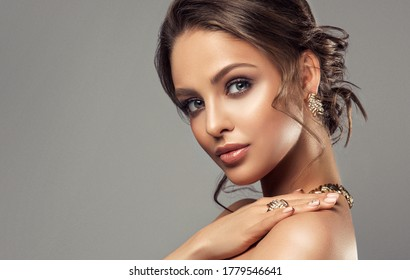 Beautiful girl with set jewelry .   Woman in a necklace with a ring and  earrings . Beauty and accessories.