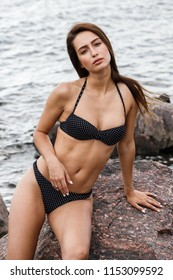 Beautiful girl sexy brown-haired posing in a swimsuit on a stone beach