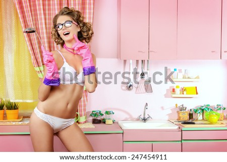 2af253d0e03 Beautiful girl in sexy lingerie alluring on her glamorous pink kitchen.  Fashion. Full length
