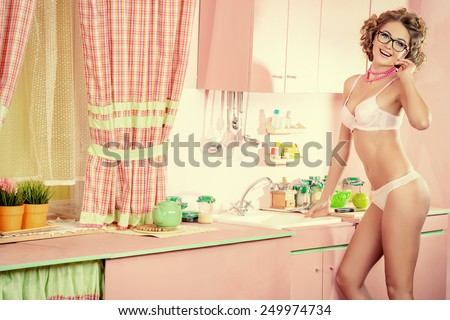 7518374cecf Beautiful girl in sexy lingerie alluring on her glamorous pink kitchen.  Fashion.