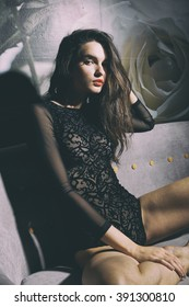 Beautiful girl in a sexy lingerie on a sofa. Fashionable photo of young sexy lady wearing black lingerie, amazing body. Glamour portrait of beautiful woman model with fresh makeup and hairstyle.