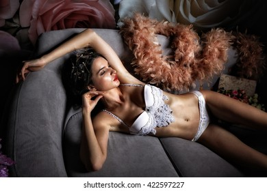 Beautiful girl in a sexy lingerie on a sofa. Fashionable photo of young sexy lady wearing white lingerie, amazing body. Glamour portrait of beautiful woman model with fresh makeup and hairstyle.