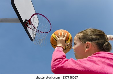 beautiful girl shooting basket and playing basketball, lower view wide angle