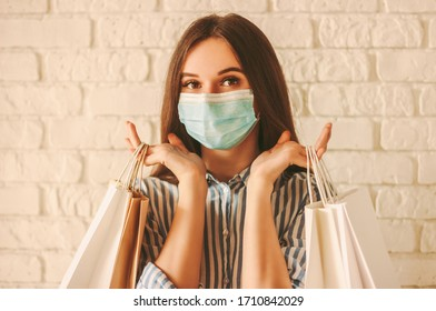Beautiful girl shopper in medical face mask holding shopping bags in hands. Young happy woman customer in protective mask on face with paper bags. Girl shopaholic. Coronavirus COVID-19, sale, discount