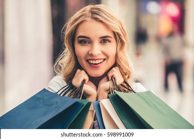 Beautiful girl with shopping bags is looking at camera and smiling while doing shopping in the mall