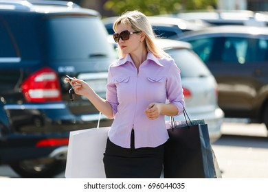 beautiful girl with shopping bags near a her car.shopping