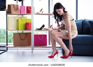 Beautiful girl shopping new shoes. Many shoes at store make her hesitate to chooses new one.
