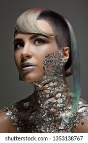Beautiful girl with a short haircut and shaved temple and dyed hair. Metallic makeup and body painting, shiny pieces of metal spangles on the lips and chest. The concept of a short haircut, color