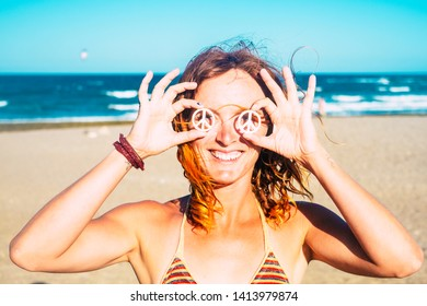 beautiful girl showing her symbol of the peace on her eyes holded with her hands - woman in bikini at the beach smiling and looking at the camer with the sun in her face