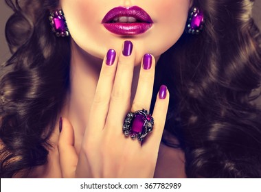 Beautiful girl showing purple manicure nails  and stylish jewelry  , ring and earrings .