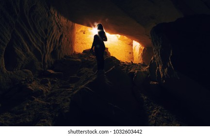 A beautiful girl silhouette in a sand cave in Jordan. Hidden cities like Petra are inside narrow caves in the mountain. A woman inside a cave digged in the mountain.