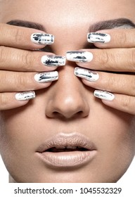 Beautiful girl with the silver metal nails. Closeup shot.