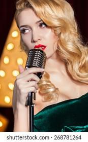 beautiful girl sings into a microphone