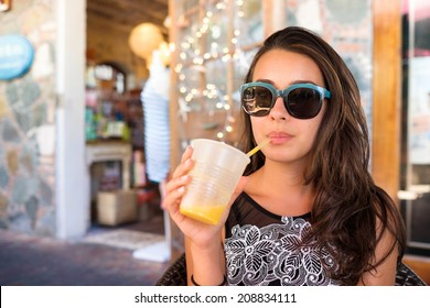 Beautiful girl sipping a smoothie outdoors in a restaurant setting.