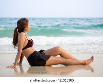 beautiful girl sit on the beach and looking to the sea