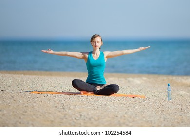 Beautiful Girl Siting At The Seaside And Meditating In Yoga Pose