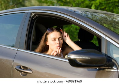 A beautiful girl sits in the car and sends an air kiss in the car mirror