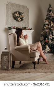 Beautiful girl sits in a chair near the fireplace and Christmas tree, and drink hot tea.