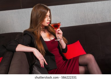 beautiful girl sits with a glass of martini