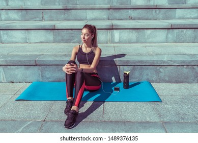 beautiful girl sits mat, fitness summer city, outdoors, yoga after workout, relaxation, enjoyment of pleasure music with headphones, active lifestyle, online application smartphone, free space