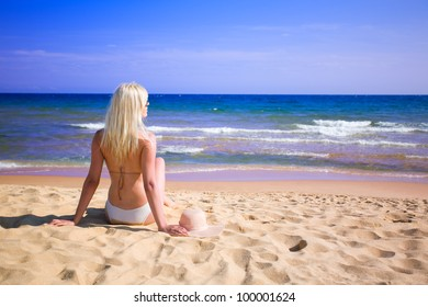 Beautiful girl sits on the beach. Polarizing filter.