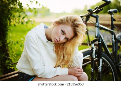 Beautiful girl sitting against bike outdoor in the park looking at you