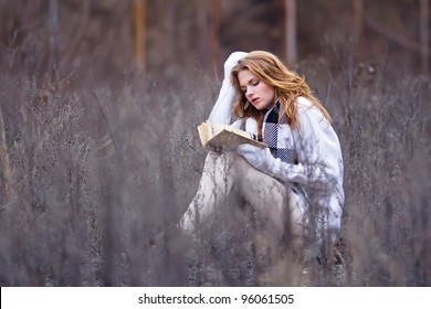 beautiful girl sitting with book in grass
