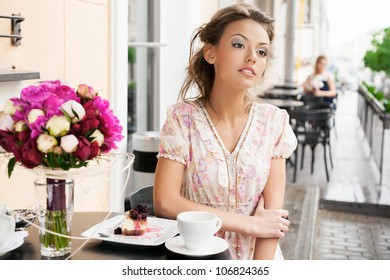 A beautiful girl are sitting in a cafe and drinking tea. Outdoors