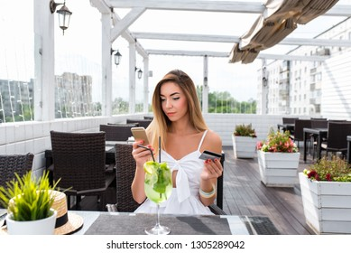 Beautiful girl sitting in a cafe on the porch in the summer, in a dress with long hair. In his hand, a plastic card and phone. A woman pays lunch or dinner with a credit card through online banking.