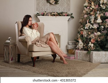 Beautiful girl sitting chair near the fireplace and the Christmas tree, and drink hot tea.