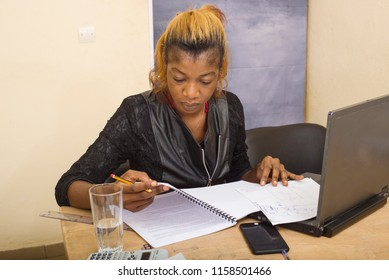 Beautiful girl sitting at a desk, holding a pencil in her hand and working on a folder